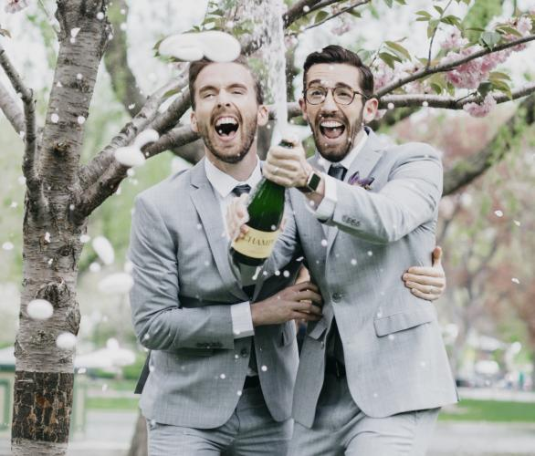 two men in suits pop a bottle of champagne