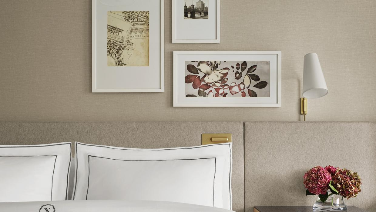 close up on bed with flowers on table and framed photos on wall